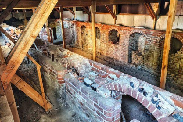 Gegenüber der Kirche St. Marien können die archäologisch freigelegten Kellerräume der Alten Schule von Wismar betrachtet werden