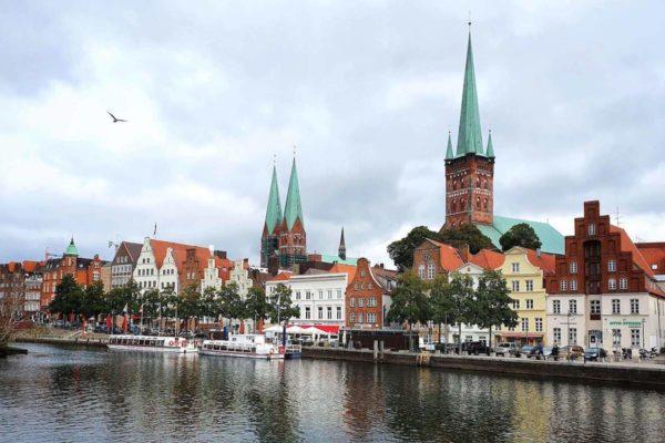 """Blick von der Trave auf die Altstadt. Lübeck wurde lange auch die """"Stadt der Sieben Türme"""" genannt, nach den fünf gotischen Hauptkirchen auf dem Altstadthügel."""