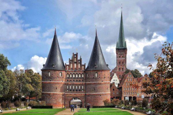 """Das Holstentor gilt als Wahrzeichen von Lübeck. Auf der Feldseite steht über dem Tor der Schriftzug """"Drinnen Eintracht, draußen Frieden."""""""