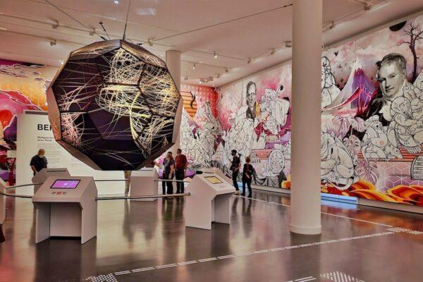 """Der erste Ausstellungsraum von """"Berlin Global"""" wird vom Wandgemälde """"Weltdenken"""" des Künstlerduos How and Nosm ausgefüllt, in dem es um kolonialen Verflechtungen Berlins und Deutschlands in der Geschichte geht."""